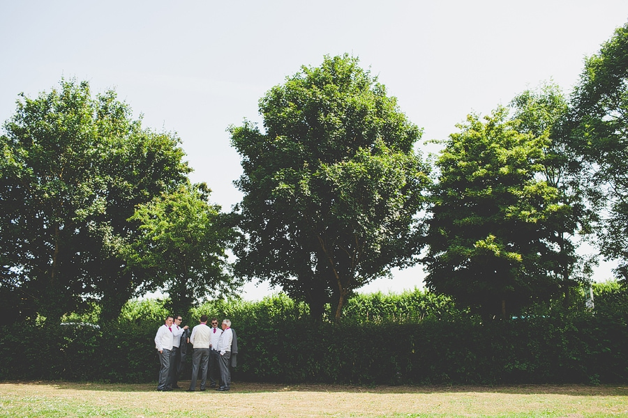 groomsmen standing in the shade