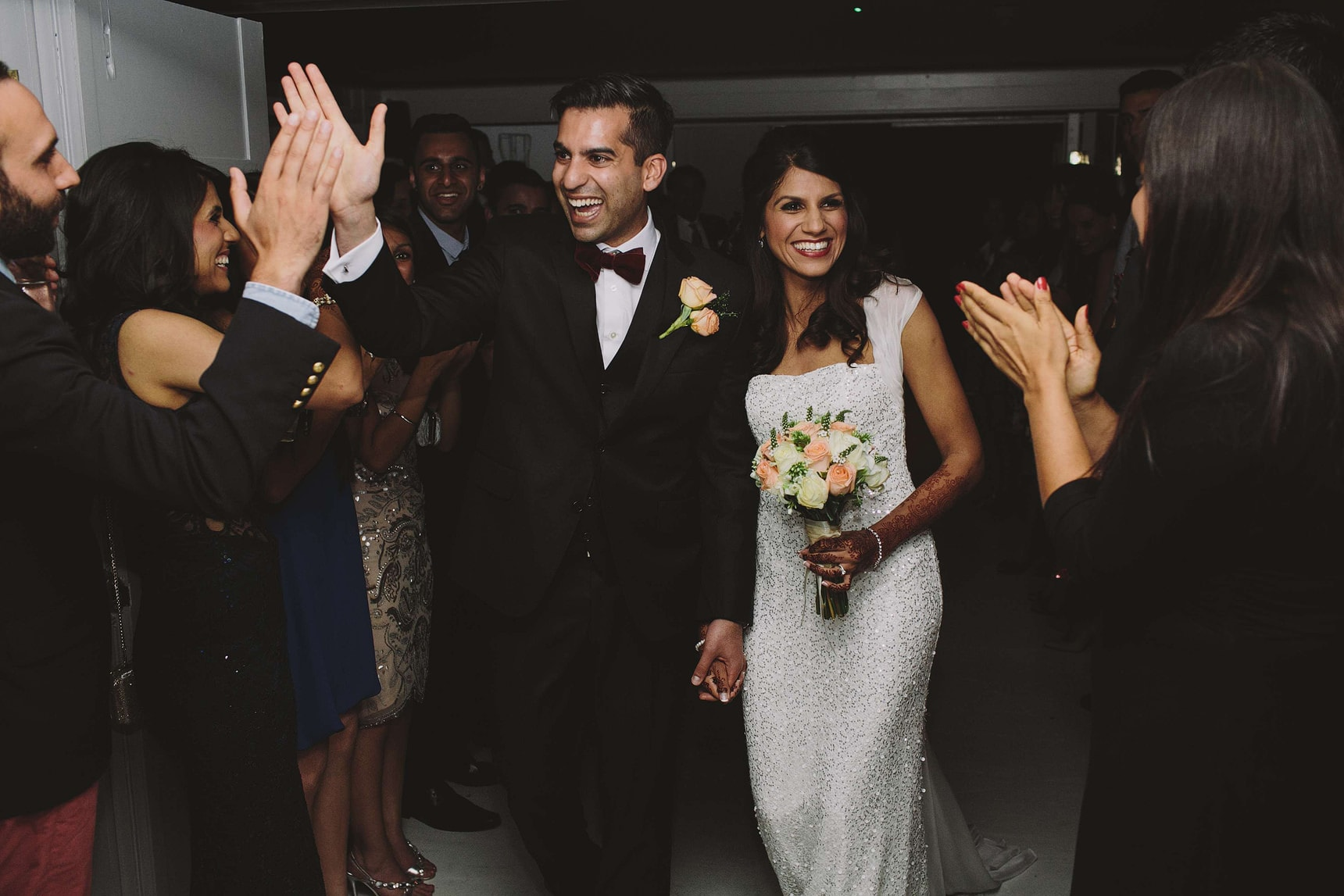 bride and groom making an entrance with a high five