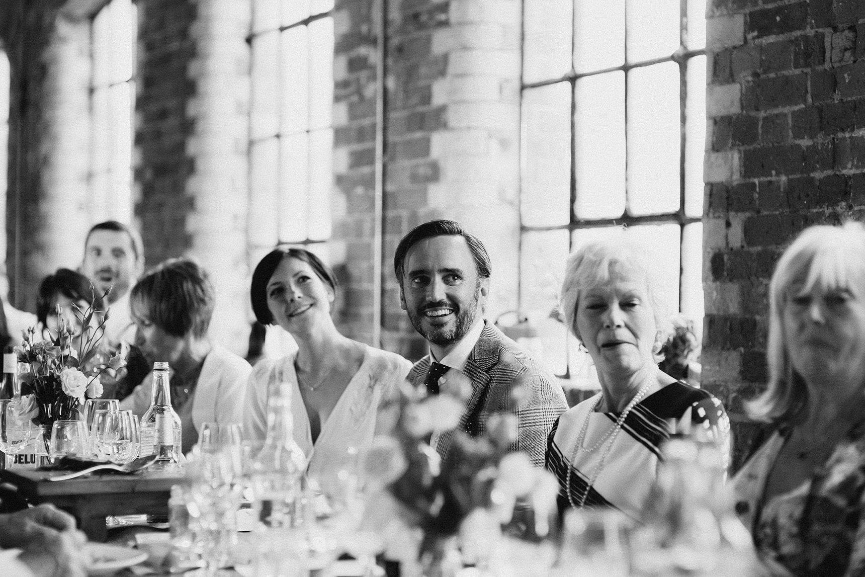 bring and groom listening to wedding speech
